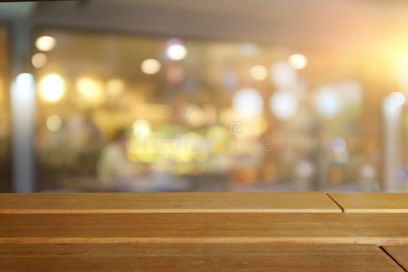 Ξύλινη κενή επιτραπέζια κορυφή πινάκων επάνω του θολωμένου υποβάθρου στοκ φωτογραφίες με δικαίωμα ελεύθερης χρήσης