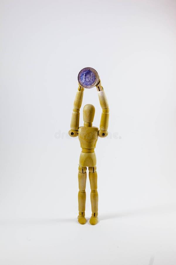 Ξύλινη κούκλα που κρατά τα ευρο- νομίσματα στοκ φωτογραφία