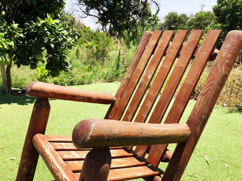 Ξύλινη λικνίζοντας καρέκλα στο χορτοτάπητα γύρω από το σπίτι στοκ εικόνες