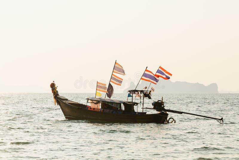 Ξύλινη μακριά βάρκα ουρών με τις ταϊλανδικές σημαίες που λικνίζουν στη θάλασσα κοντά στην παραλία Railey στην επαρχία Krabi, Ταϊλ στοκ εικόνες