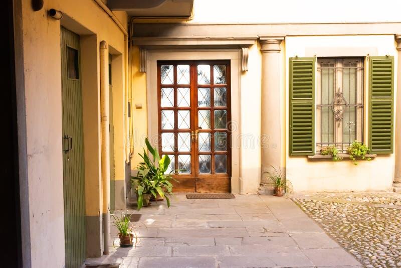 Ξύλινη μπροστινή πόρτα έξω από το παλαιό ιταλικό σπίτι στο Μπέργκαμο, Ιταλία στοκ εικόνα