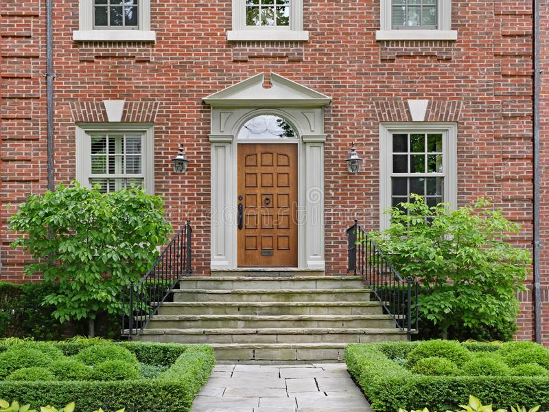 Ξύλινη μπροστινή πόρτα του μεγάλου σπιτιού τούβλου στοκ φωτογραφία