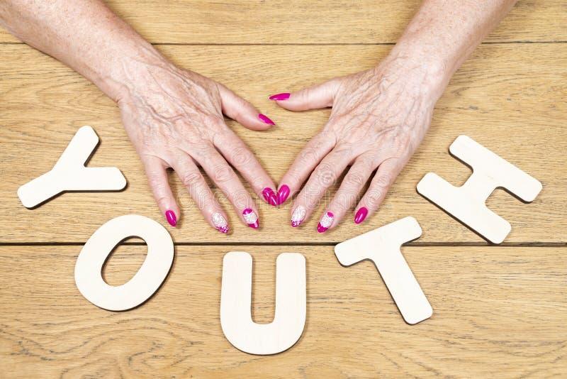 Ξύλινη νεολαία λέξης και παλαιά χέρια στοκ φωτογραφία με δικαίωμα ελεύθερης χρήσης