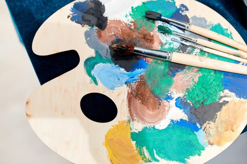 Ξύλινη παλέτα για την γκουας αναπαραγωγής με χρώμα και τέσσερις βούρτ στοκ εικόνα με δικαίωμα ελεύθερης χρήσης