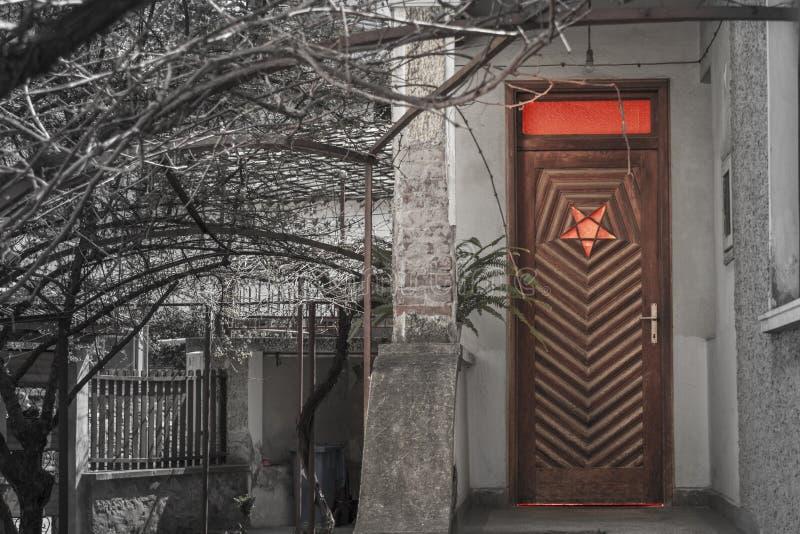 Ξύλινη πόρτα εισόδων σε ένα σπίτι με αντιστρεμμένος pentagram στοκ εικόνες