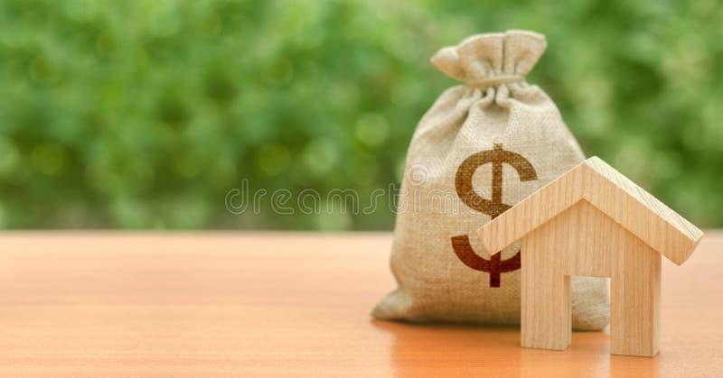 Ξύλινη φιγούρα και τσάντα με το σύμβολο του δολαρίου Προϋπολογισμός, επιδοτούμενα κεφάλαια Ενυπόθηκο δάνειο για την αγορά κατοικι στοκ φωτογραφίες