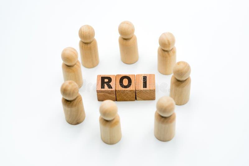 Ξύλινοι αριθμοί ως επιχειρησιακή ομάδα στον κύκλο γύρω από τη απόδοση της επένδυσης αρκτικολέξων ROI στοκ εικόνα