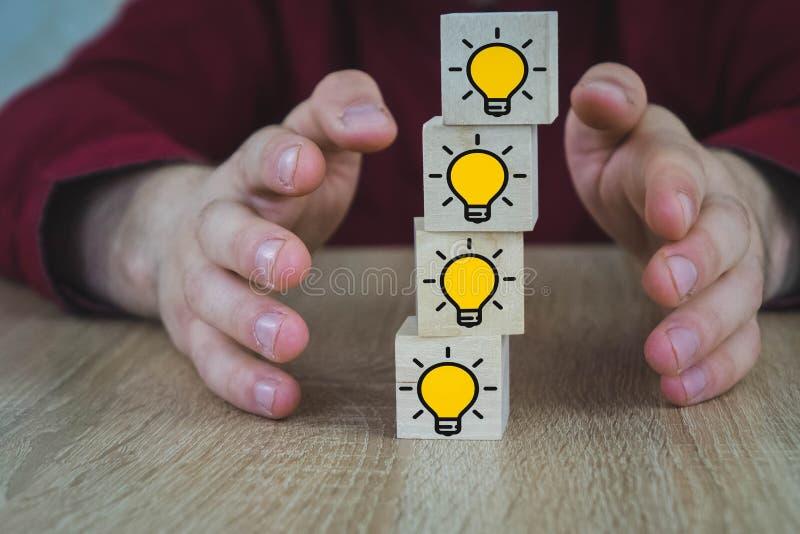 Ξύλινοι κύβοι που στέκονται ο ένας επάνω από τον άλλον με την εικόνα ενός καίγοντας λαμπτήρα, ο οποίος συμβολίζει τη νέα ιδέα, η  στοκ εικόνες με δικαίωμα ελεύθερης χρήσης
