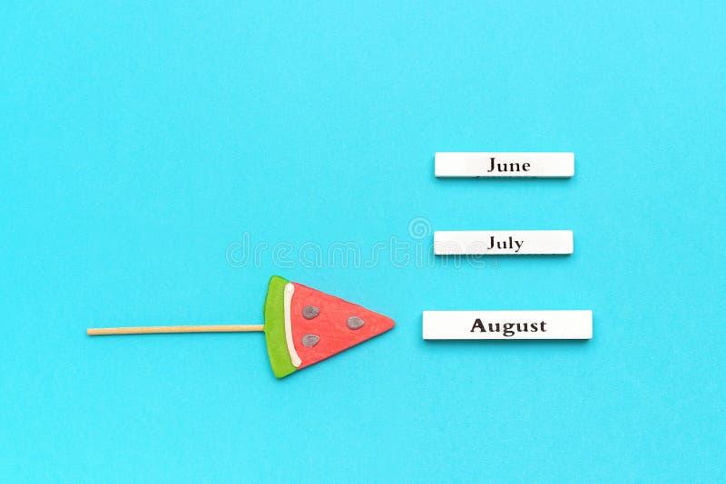 Ξύλινοι μήνες ημερολογιακού καλοκαιριού Αύγουστος, Ιούνιος, Ιούλιος και καρπούζι lollipop στο ραβδί στο μπλε υπόβαθρο Διακοπές έν στοκ φωτογραφία με δικαίωμα ελεύθερης χρήσης