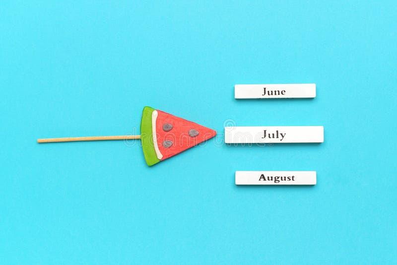 Ξύλινοι μήνες ημερολογιακού καλοκαιριού Ιούλιος, Ιούνιος, Αύγουστος και καρπούζι lollipop στο ραβδί στο μπλε υπόβαθρο Διακοπές έν στοκ εικόνες