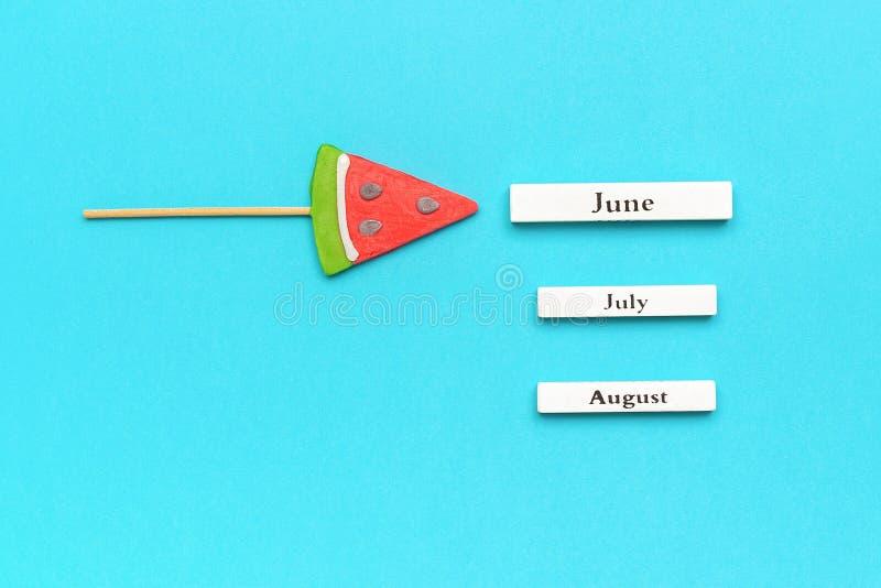 Ξύλινοι μήνες ημερολογιακού καλοκαιριού Ιούνιος, Ιούλιος, Αύγουστος και καρπούζι lollipop στο ραβδί στο μπλε υπόβαθρο Διακοπές έν στοκ φωτογραφίες με δικαίωμα ελεύθερης χρήσης