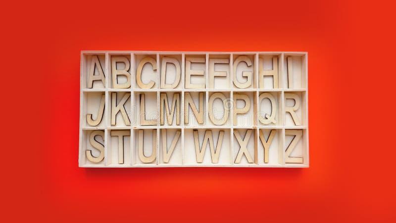 Ξύλινοι φραγμοί αλφάβητου με τις επιστολές - κιβώτιο σε ένα κόκκινο υπόβαθρο αγγλική εκμάθηση στοκ εικόνες