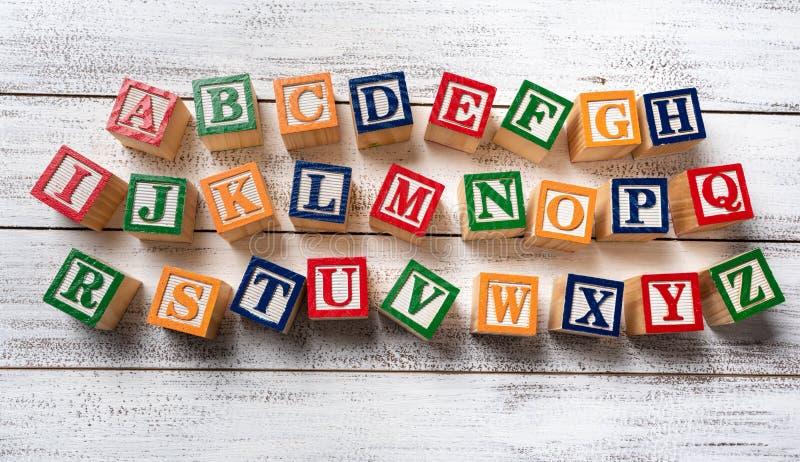 Ξύλινοι φραγμοί επιστολών που κάνουν το αλφάβητο στο άσπρο ξύλινο υπόβαθρο στοκ εικόνες