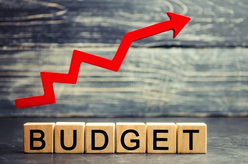 """Ξύλινοι φραγμοί και η επιγραφή """"προϋπολογισμός """"και το επάνω βέλος Έννοια της επιχειρησιακής επιτυχίας, της οικονομικής αύξησης κ στοκ φωτογραφία"""