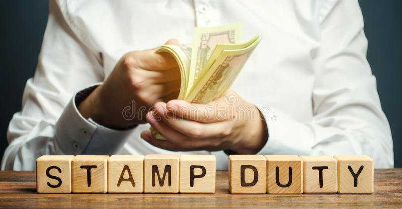 Ξύλινοι φραγμοί με το τέλος χαρτοσήμου λέξης και χρήματα στα χέρια ενός επιχειρηματία Φόρος που επιβάλλεται στα έγγραφα Φόροι που στοκ εικόνες