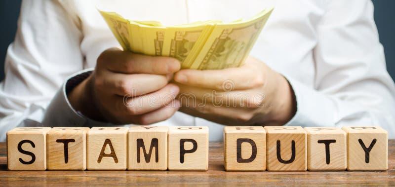 Ξύλινοι φραγμοί με το τέλος χαρτοσήμου λέξης και χρήματα στα χέρια ενός επιχειρηματία Φόρος που επιβάλλεται στα έγγραφα Φόροι που στοκ φωτογραφία