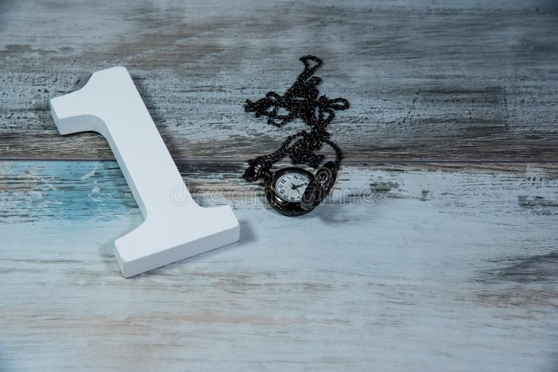 Ξύλινος αριθμός ένα και ρολόι που μετρά το χρόνο στοκ εικόνα με δικαίωμα ελεύθερης χρήσης