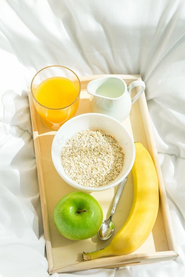 Ξύλινος δίσκος με τα υγιή συστατικά προγευμάτων στα άσπρα γενικά κλινοσκεπάσματα Βρώμες στο γάλα κύπελλων στην μπανάνα Apple χυμο στοκ εικόνα