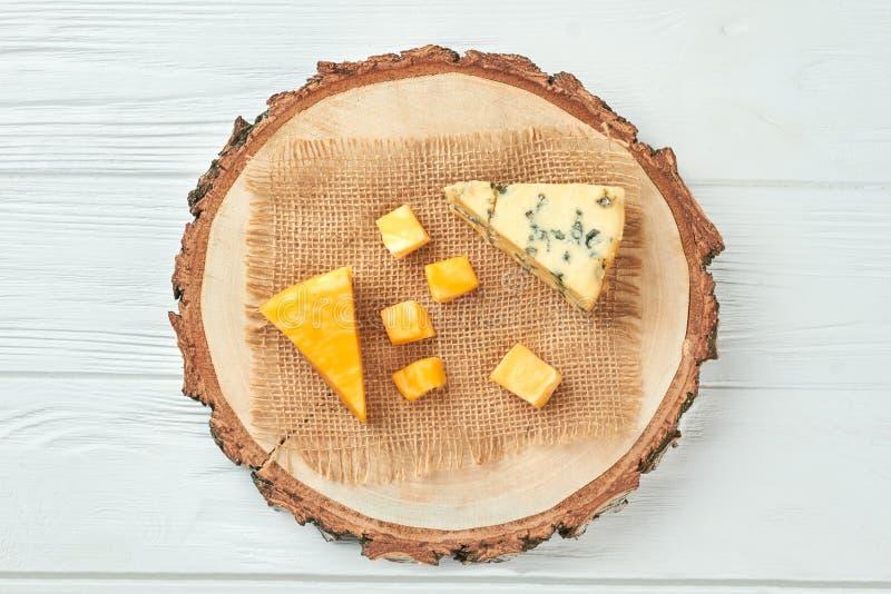 Ξύλινος δίσκος με τους διαφορετικούς τύπους τυριών στοκ εικόνες με δικαίωμα ελεύθερης χρήσης