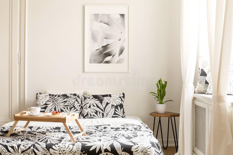 Ξύλινος δίσκος με το πρόγευμα σε ένα διπλό κρεβάτι με τη floral κλινοστρωμνή ι στοκ εικόνες
