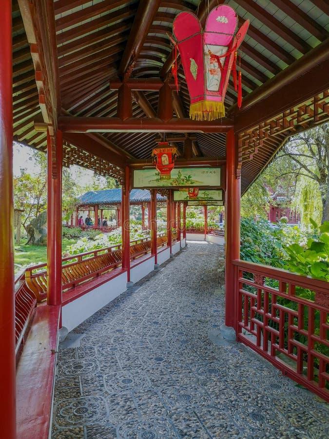 Ξύλινος διάδρομος παραδοσιακού κινέζικου στο δονούμενο κόκκινο με τα φανάρια στον κινεζικό κήπο σε Pairi Daiza στοκ φωτογραφία με δικαίωμα ελεύθερης χρήσης