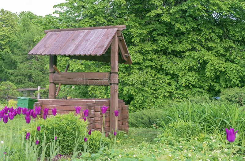 Ξύλινος καλά στο χωριό Ξύλινος καλά στο υπόβαθρο του πράσινου φυλλώματος στοκ εικόνα