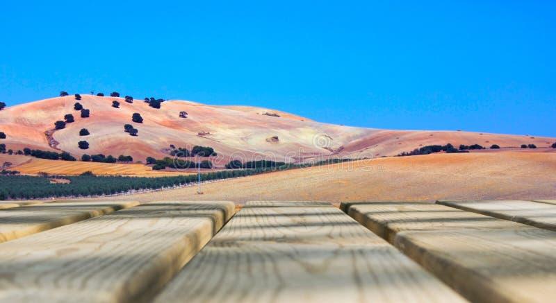 Ξύλινος κενός πίνακας πινάκων μπροστά από το υπόβαθρο μπλε ουρανού & βουνών Ξύλινο πάτωμα προοπτικής κατά τη διάρκεια του τομέα κ στοκ εικόνα