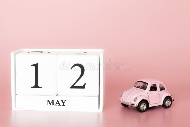 Ξύλινος κύβος κινηματογραφήσεων σε πρώτο πλάνο 12ος του Μαΐου Η ημέρα 12 μπορεί μήνας, ημερολόγιο σε ένα ρόδινο υπόβαθρο με στοκ φωτογραφίες