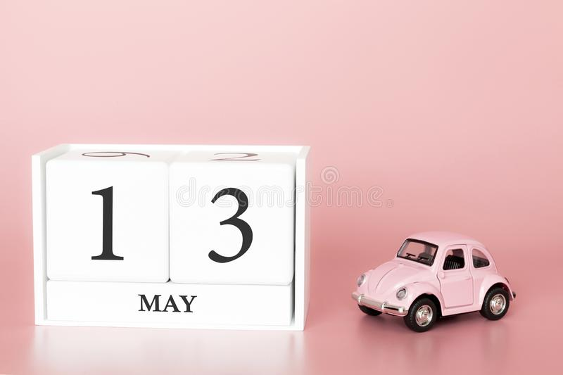 Ξύλινος κύβος κινηματογραφήσεων σε πρώτο πλάνο 13ος του Μαΐου Η ημέρα 13 μπορεί μήνας, ημερολόγιο σε ένα ρόδινο υπόβαθρο με στοκ εικόνες