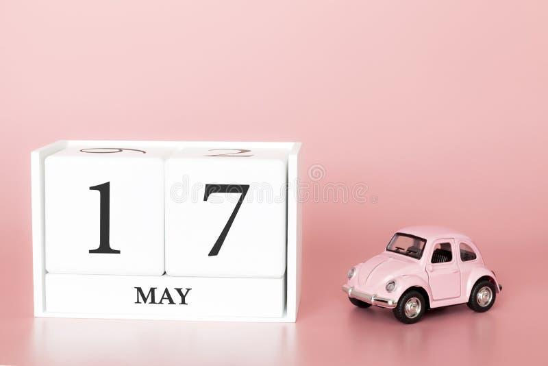 Ξύλινος κύβος κινηματογραφήσεων σε πρώτο πλάνο 17ος του Μαΐου Η ημέρα 17 μπορεί μήνας, ημερολόγιο σε ένα ρόδινο υπόβαθρο με στοκ εικόνες