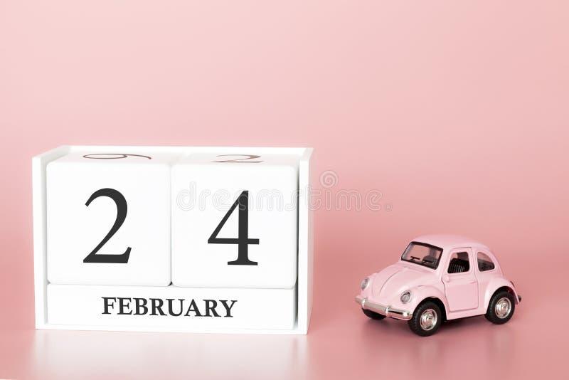 Ξύλινος κύβος κινηματογραφήσεων σε πρώτο πλάνο 24ος του Φεβρουαρίου Ημέρα 24 του μήνα Φεβρουαρίου, ημερολόγιο σε ένα ροζ στοκ εικόνες