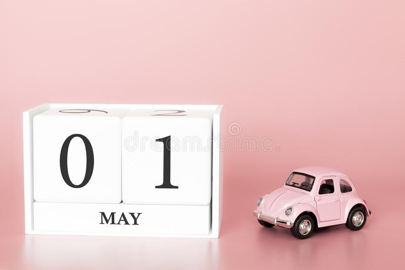 Ξύλινος κύβος 1$ος κινηματογραφήσεων σε πρώτο πλάνο του Μαΐου Η ημέρα 1 μπορεί μήνας, ημερολόγιο σε ένα ρόδινο υπόβαθρο με στοκ φωτογραφία