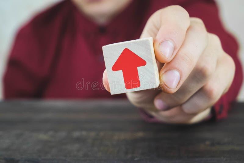 ξύλινος κύβος στο χέρι ενός ατόμου με ένα κόκκινο βέλος, κόκκινη αύξηση και ανάπτυξη μέσων στοκ φωτογραφία