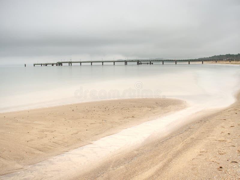 Ξύλινος λιμενοβραχίονας και στο μπλε ηλιοβασίλεμα λιμνών και το νεφελώδη ουρανό στοκ φωτογραφία με δικαίωμα ελεύθερης χρήσης