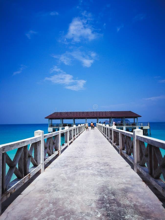 Ξύλινος λιμενοβραχίονας στο μεσημέρι κάτω από τους σαφείς μπλε ουρανούς με το περπάτημα ανθρώπων στοκ φωτογραφίες με δικαίωμα ελεύθερης χρήσης