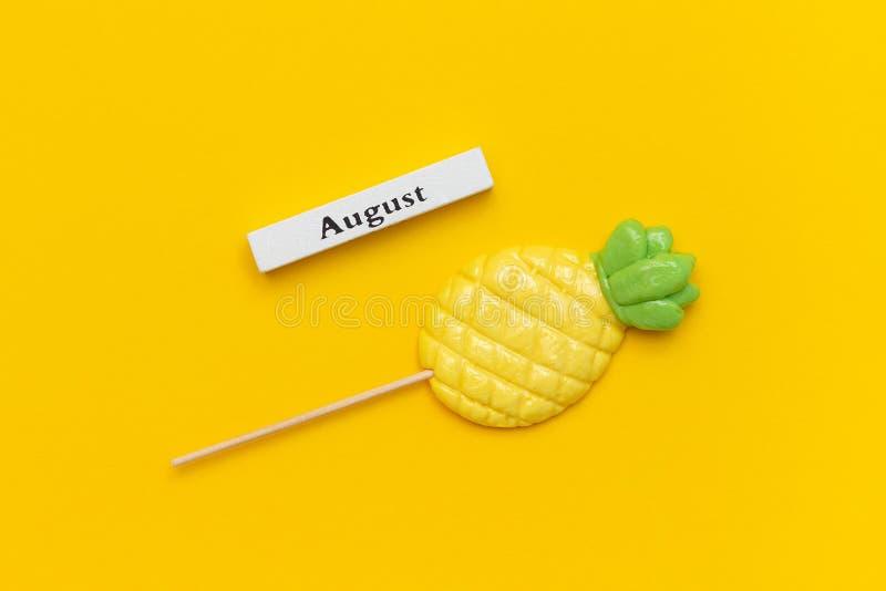 Ξύλινος μήνας Αύγουστος ημερολογιακού καλοκαιριού και ανανάς lollipop στο ραβδί στο κίτρινο υπόβαθρο Διακοπές έννοιας, διακοπές ή στοκ φωτογραφίες
