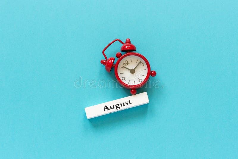 Ξύλινος μήνας Αύγουστος ημερολογιακού καλοκαιριού και κόκκινο ξυπνητήρι στο μπλε υπόβαθρο εγγράφου Έννοια γειά σου Αύγουστος ή αν στοκ φωτογραφία με δικαίωμα ελεύθερης χρήσης