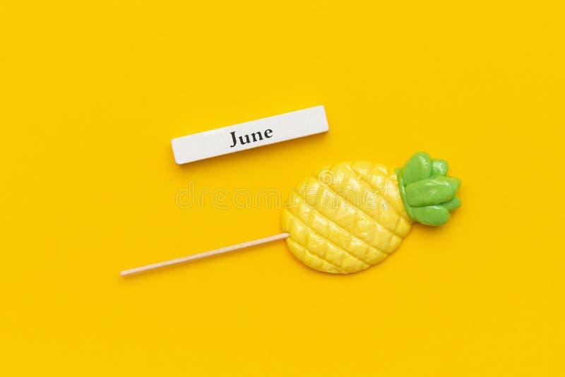 Ξύλινος μήνας Ιούνιος ημερολογιακού καλοκαιριού και ανανάς lollipop στο ραβδί στο κίτρινο υπόβαθρο Διακοπές έννοιας, διακοπές ή γ στοκ εικόνα με δικαίωμα ελεύθερης χρήσης
