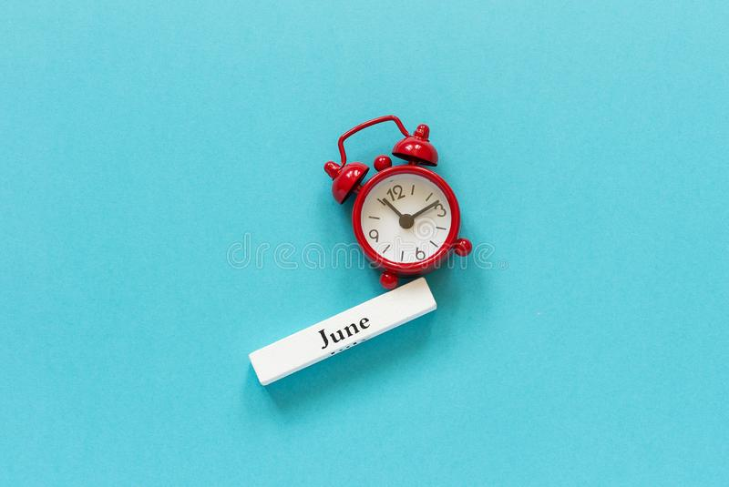 Ξύλινος μήνας Ιούνιος ημερολογιακού καλοκαιριού και κόκκινο ξυπνητήρι στο μπλε υπόβαθρο εγγράφου Έννοια γειά σου Ιούνιος ή αντίο  στοκ φωτογραφία