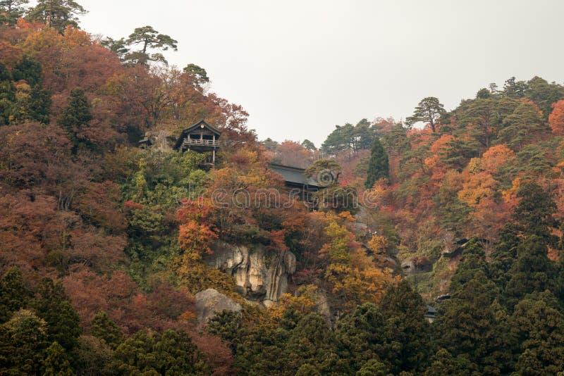 Ξύλινος ναός στο βουνό κατά τη διάρκεια της δασικής αλλαγής φύλλων στο πορτοκάλι στοκ εικόνα