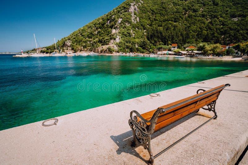 Ξύλινος πάγκος μπροστά από τη θάλασσα Ecovillage στο νησί Ithaca στην Ελλάδα Γραφική μεσογειακή πόλη στοκ εικόνες