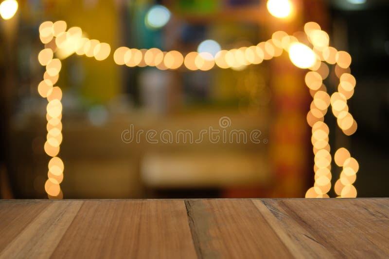 Ξύλινος πίνακας καφετιού στο μπροστινό θολωμένο θερμό υπόβαθρο bokeh στοκ φωτογραφίες
