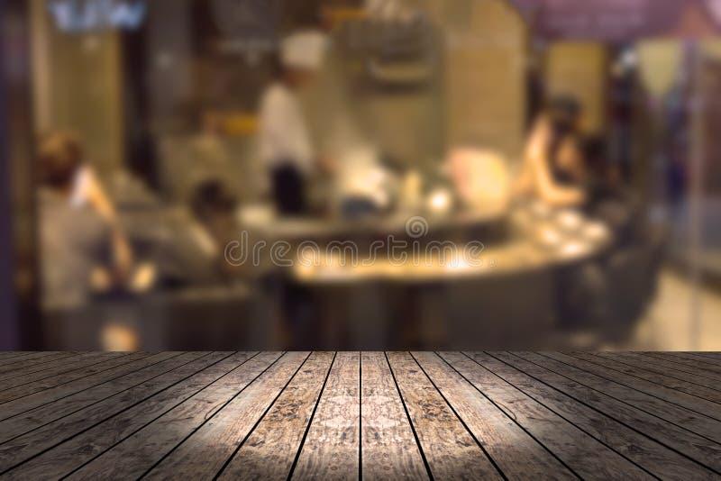 Ξύλινος πίνακας με το υπόβαθρο εστιατορίων θαμπάδων στοκ εικόνες