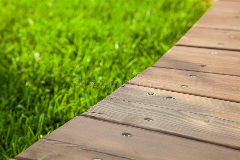 Ξύλινος πίνακας στη διαγώνιος στην εικόνα με το θολωμένο θερινό πράσινο υπόβαθρο στοκ εικόνες