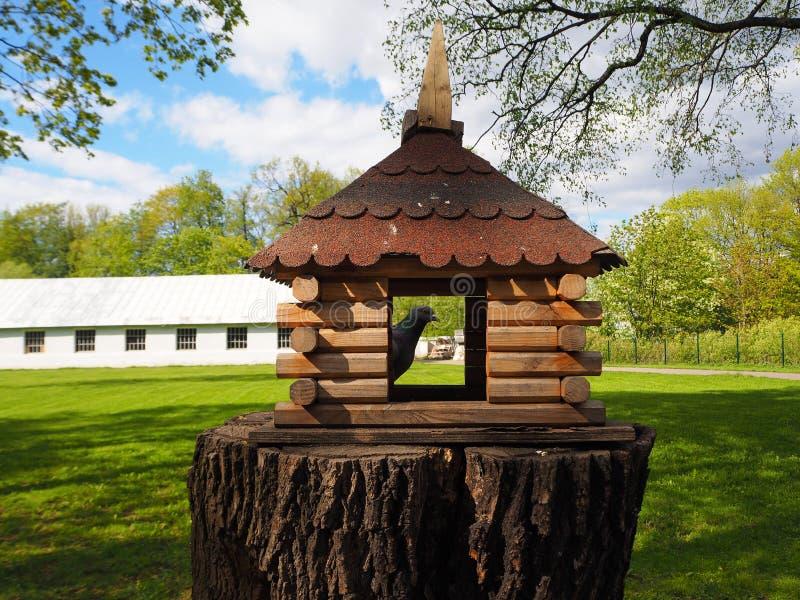 Ξύλινος που χαράζεται birdhouse σε ένα κολόβωμα δέντρων, ένας τροφοδότης για τα πουλιά με ένα περιστέρι σε το στοκ φωτογραφία