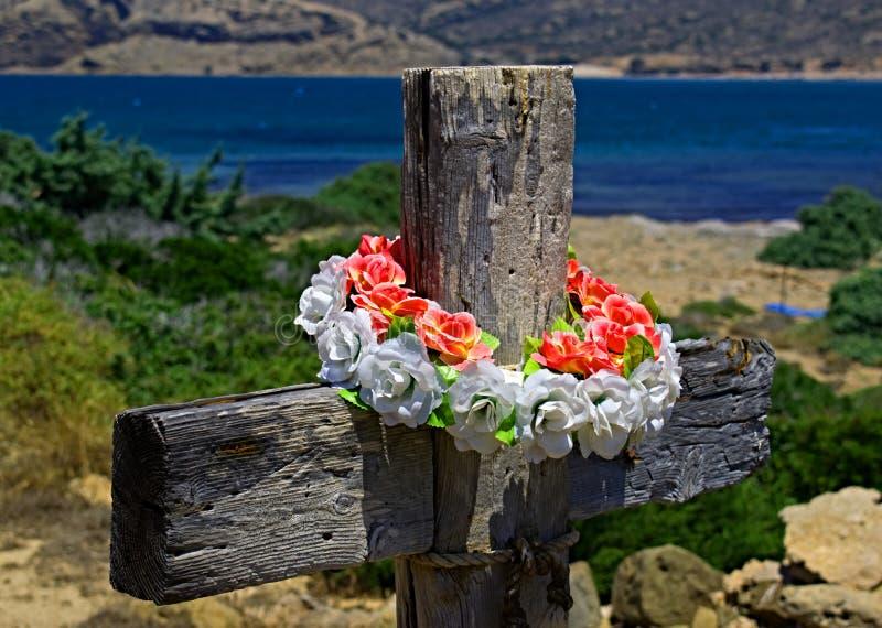 Ξύλινος σταυρός με το στεφάνι στο υπόβαθρο της ακτής στοκ φωτογραφία