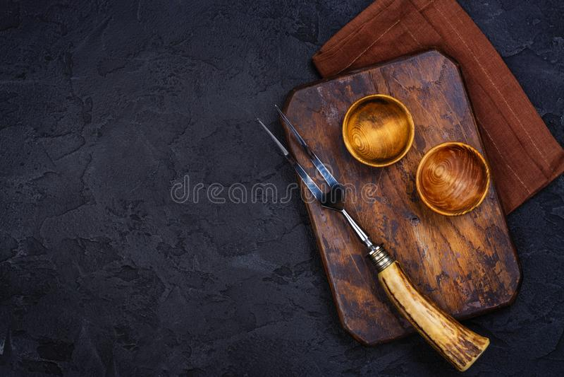 Ξύλινος τέμνων πίνακας, κύπελλο για τα καρυκεύματα και το εκλεκτής ποιότητας δίκρανο και μαχαίρι στο μαύρο υπόβαθρο πετρών στοκ εικόνες