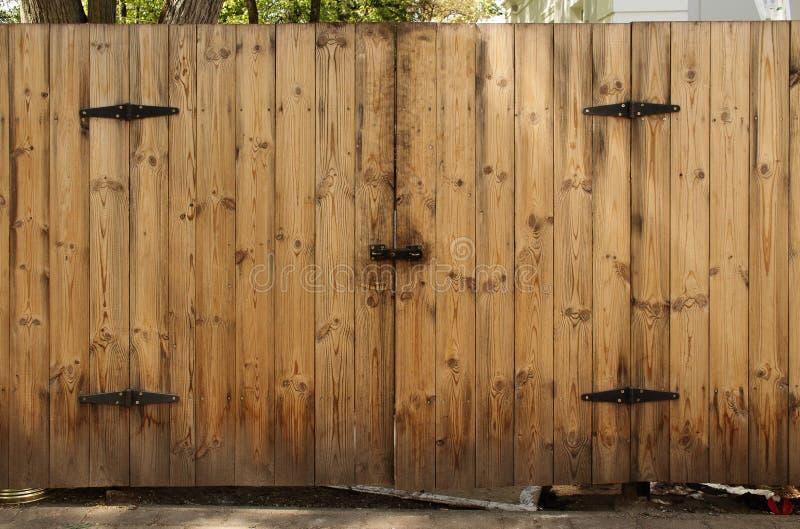 Ξύλινος φράκτης σανίδων με την κλειστή πόρτα πυλών με τις μαύρες λεπτομέρειες σιδήρου και το μπουλόνι κλειδαριών στοκ εικόνα