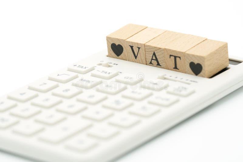 Ξύλινος Φ.Π.Α λέξης και ξύλινη καρδιά που τοποθετούνται σε έναν άσπρο υπολογιστή ως έννοια χρηματοδότησης υποβάθρου και επιχειρησ στοκ εικόνα