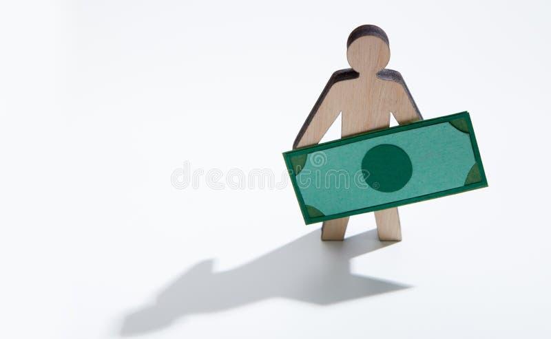 Ξύλινο άτομο με τα δολάρια που στέκονται στο άσπρο υπόβαθρο στοκ φωτογραφία